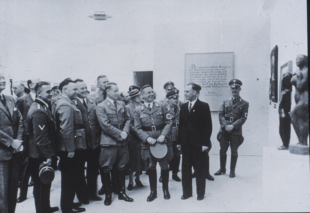 nazi officers in uniform looking at art