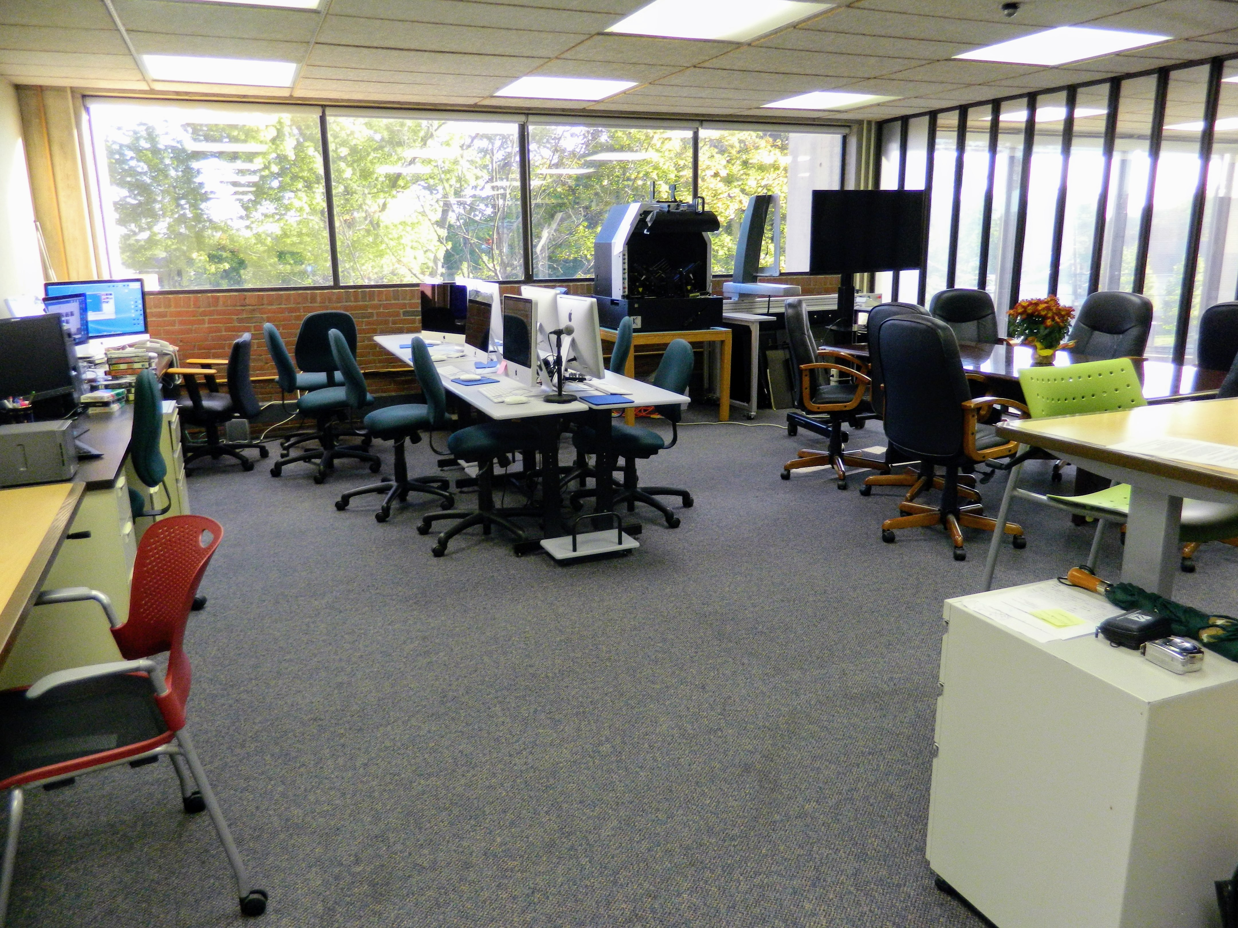 interior of room with computers and desks/ digital service lab