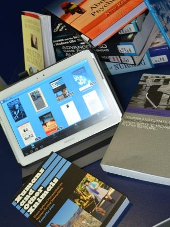 Ebook on a mobile device in a pile of paper books