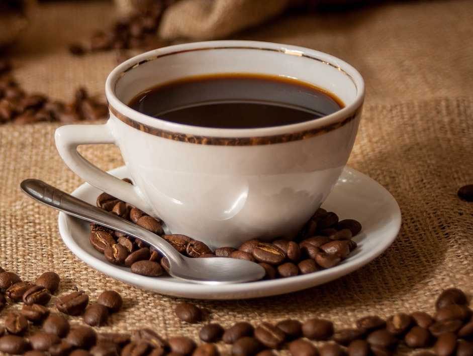 Cup of coffee on saucer with spoon, coffee beans, sacks of coffee beans