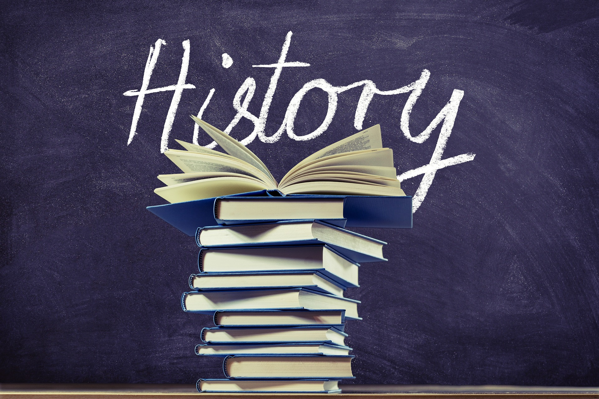 History written on chalkboard with stack of books.