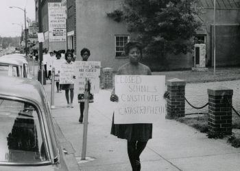 line of african american women carrying protesting signs for school closings