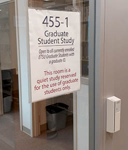 """A photograph showing the entrance to the Graduate Study Room in Sherrod Library. An ID card reader and sign are pictured. The text on the sign reads, """"Room 455-1. Graduate Student Study. Open to all currently enrolled ETSU graduate students with an ETSU ID. This room is a quiet study reserved for the use of graduate students only."""""""