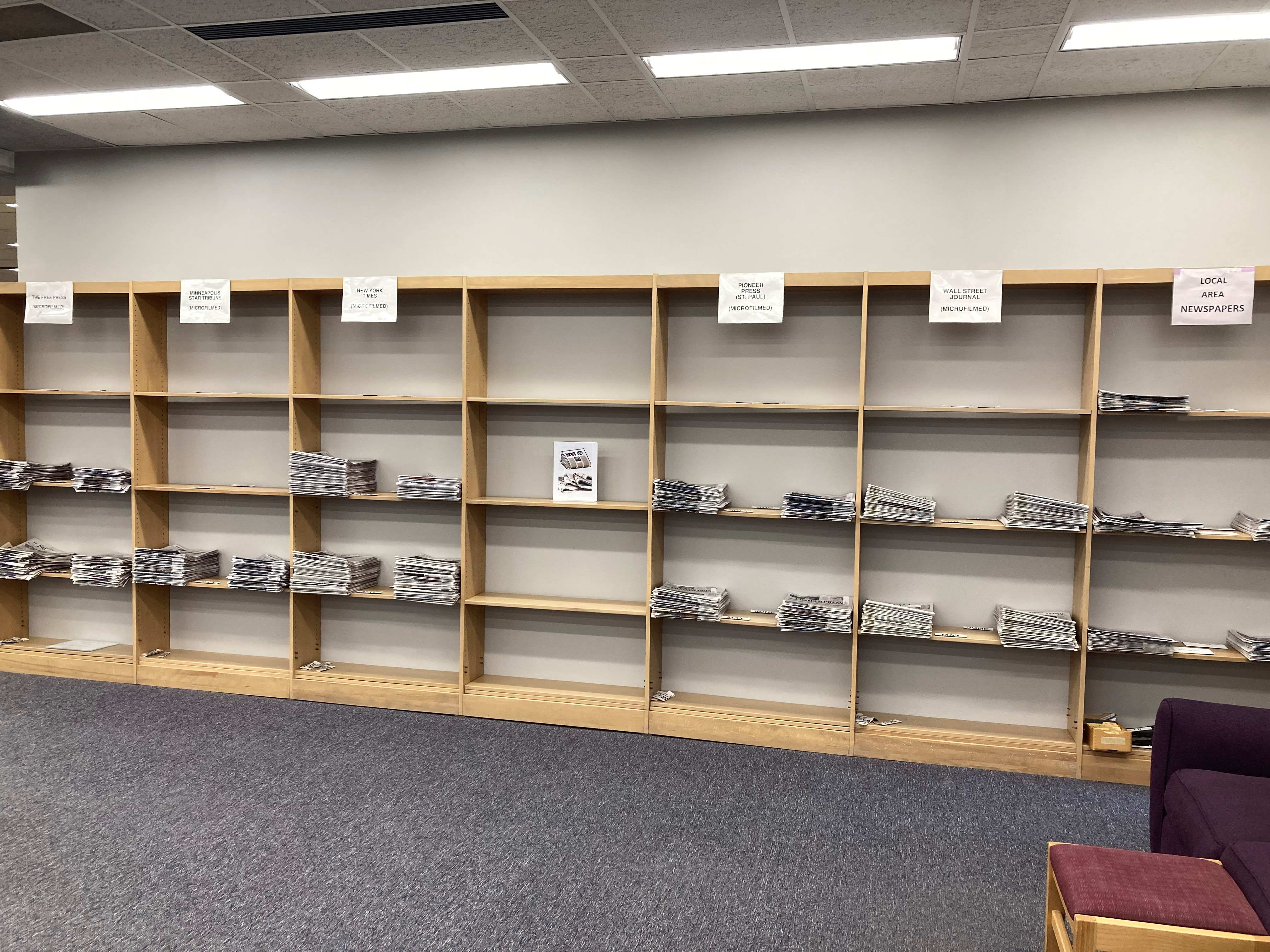 the newspaper area has shelves of current newspapers organized by date