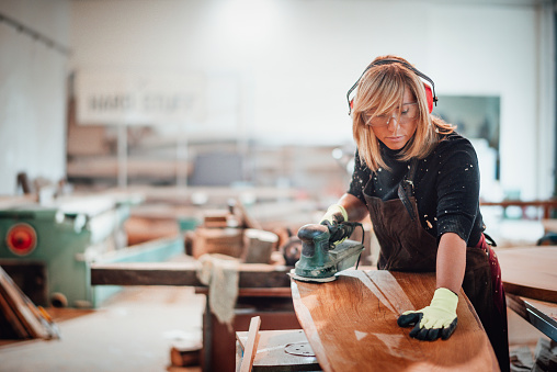 carpentry picture of woman in black shirt sanding wood