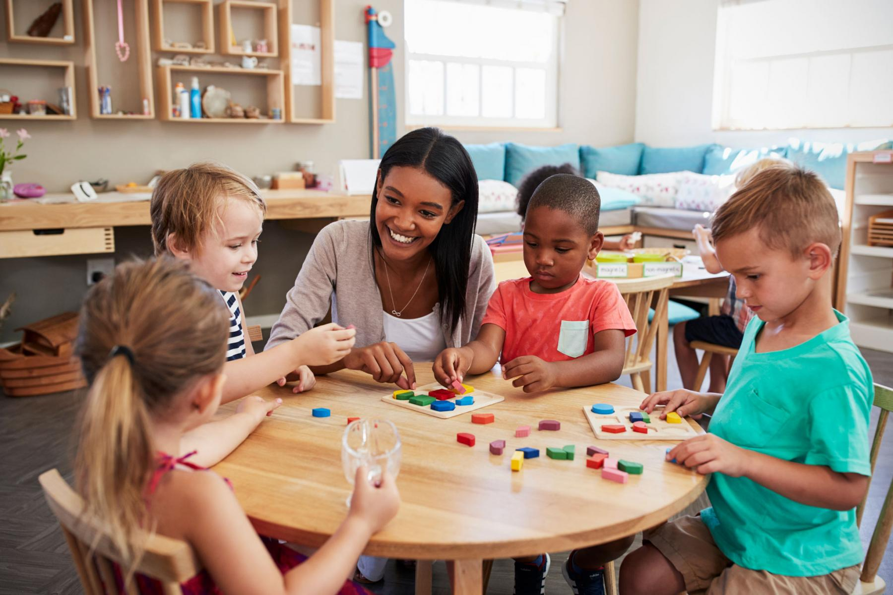 early childhood education woman with black and white children playing with red, blue and green dots at wooden table