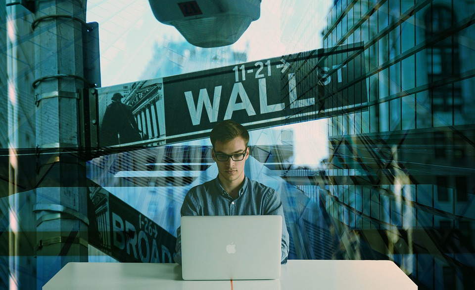 economic man wearing glasses sitting at table with laptop with a wall street sign in the teal background