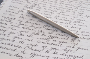 english and writing white notebook paper with cursive writing and silver pen on top