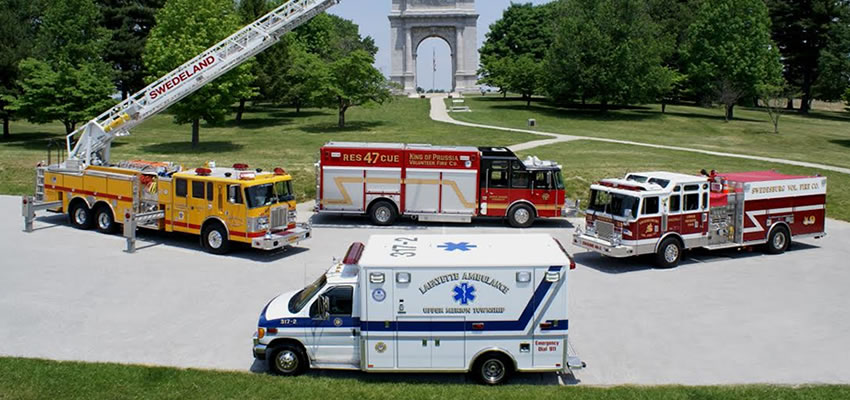 fire protection and ems picture with fire and ems trucks on pavement; green grass with sidewalk