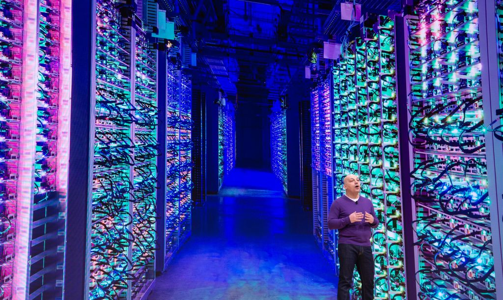 mission critical operations picture of man in purple shirt standing in a server room with purple, blue green colors
