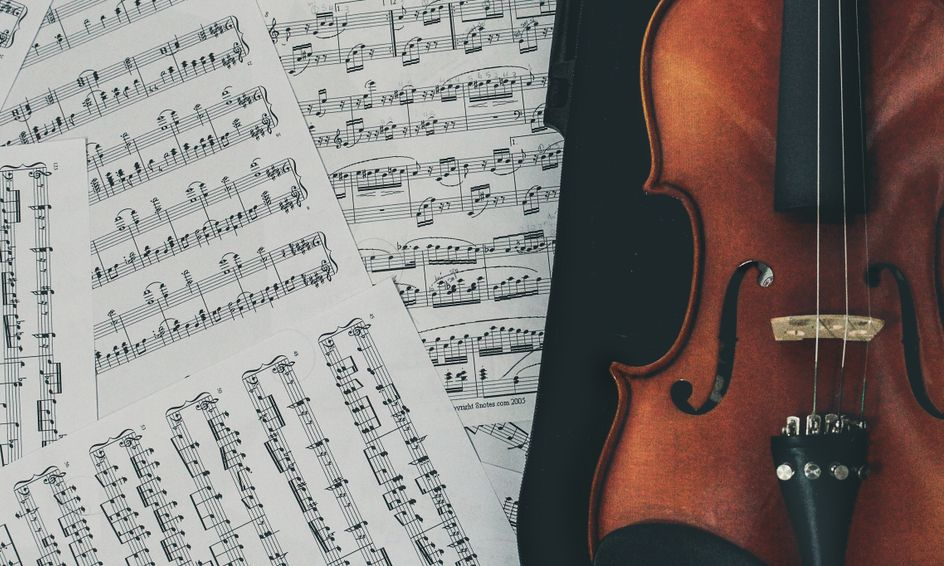 music appreciation photo with music notes on white paper and brown violin