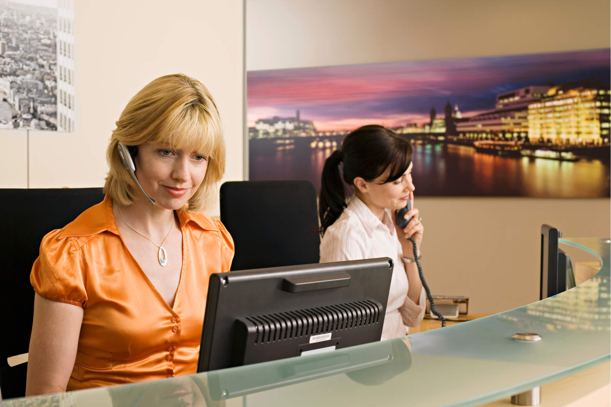 office systems technology picture of two women at a desk wit phone earpiece in ear looking at a computer with orange shirt and white shirt