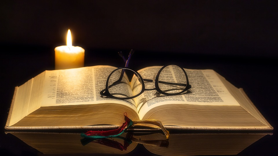 religion picture of book open with a pair of black glasses on top with a candle lit in a black background