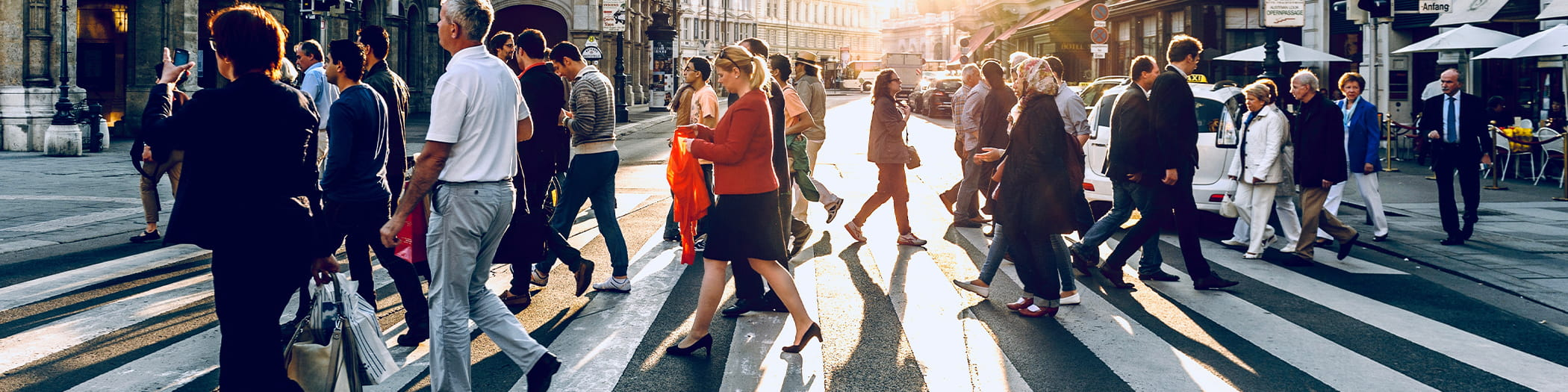sociology picture with men and women walking across the street in a city in casual and work attire in blue, white, red and black colors