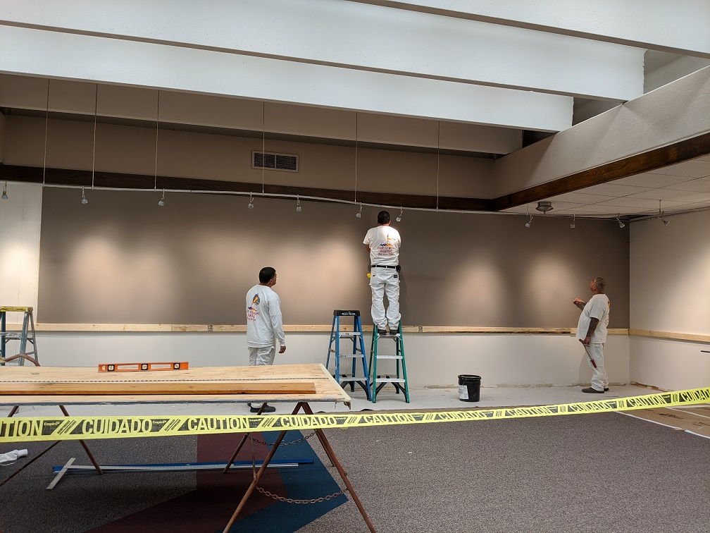 Contractors checking to make sure the seam between the two wall coverings is straight