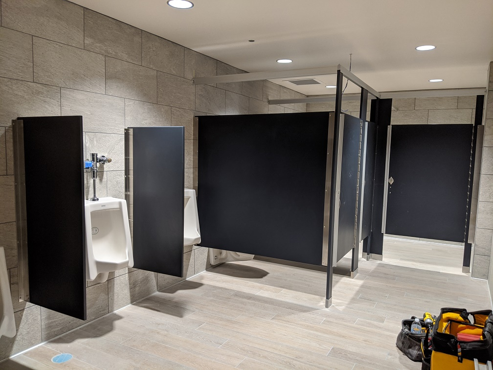Remodeled library restroom in gray tiles and partitions