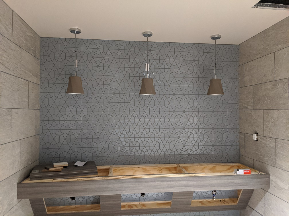 Pendant lights over unfinished counter with gray tiles in background
