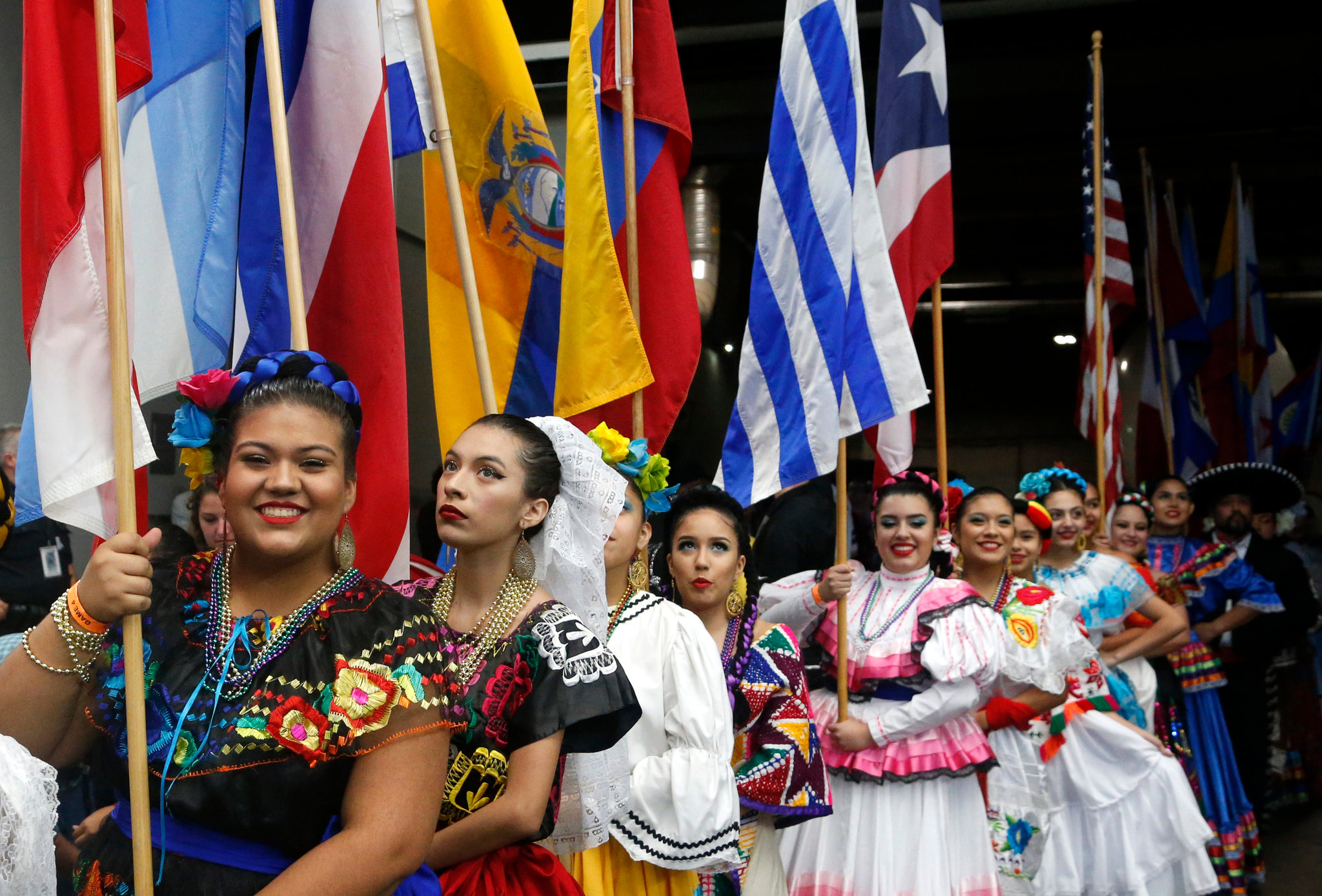 Latina women in cultural clothing carrying flags