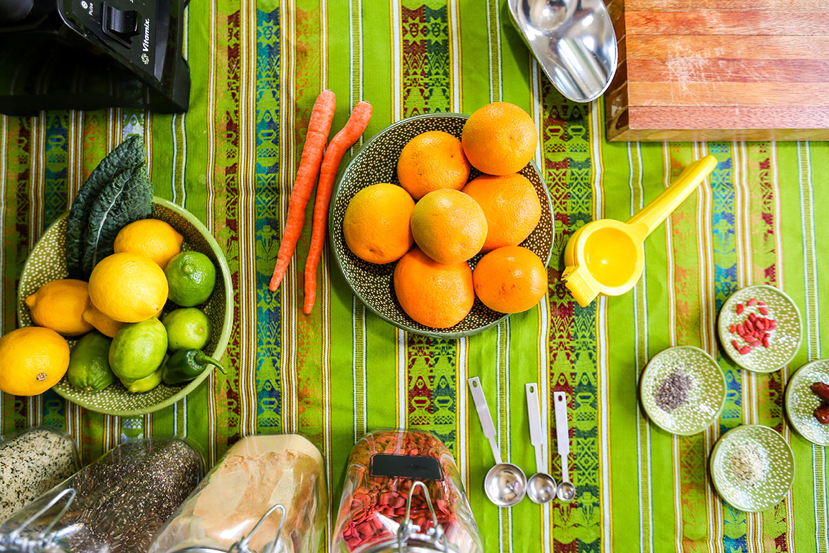 woven tablecloth, bowls of ingredients like oranges, carrots, kale