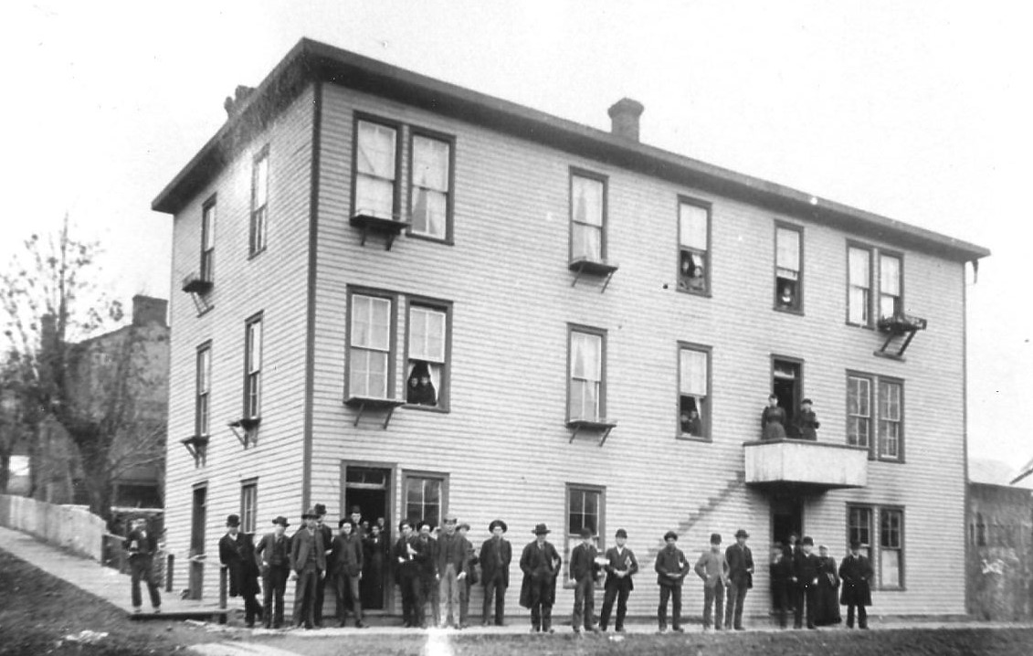 Black & white photo of Barrett Home with students posing in front of the building, on the veranda, and looking out of the windows.