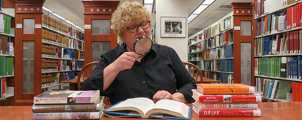 Deb Smith-Cohen, surrounded by mysteries, holds a magnifying glass.