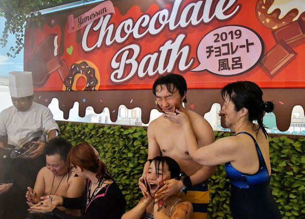 Bathers paint each other with chocolate sauce at a hot springs spa resort in Hakone, Kanagawa prefecture, Japan on February 2, 2019.