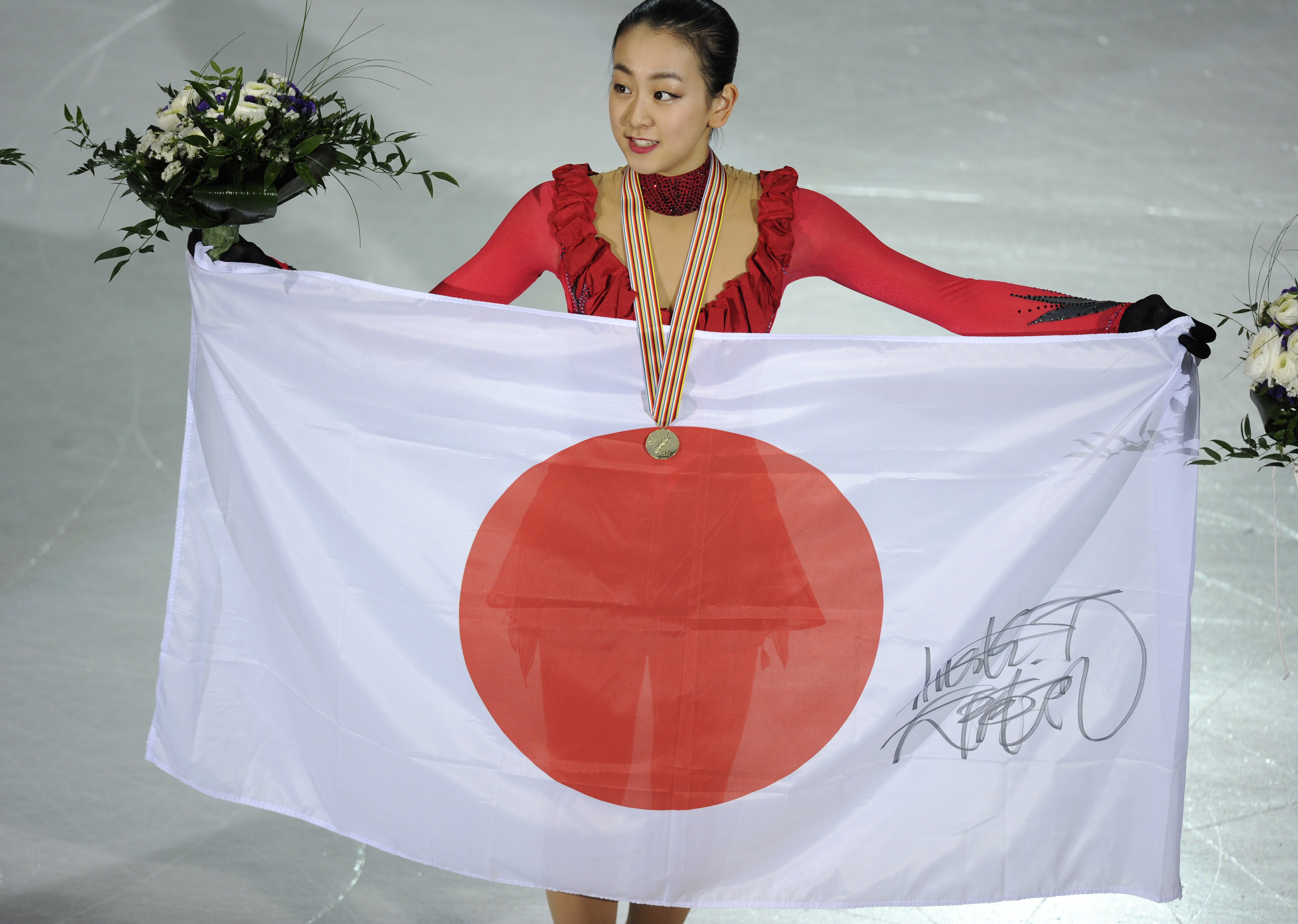 Gold Medalist Japan's Mao Asada Holds a Japan's Flag as She Poses