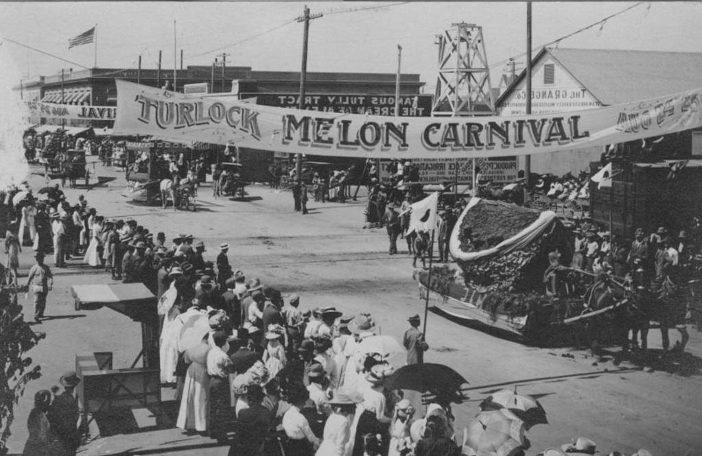 Historical photograph of a parade with a banner that reads, 'Turlock Melon Carnival.'