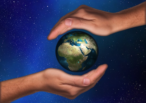 Earth being encased in human hands