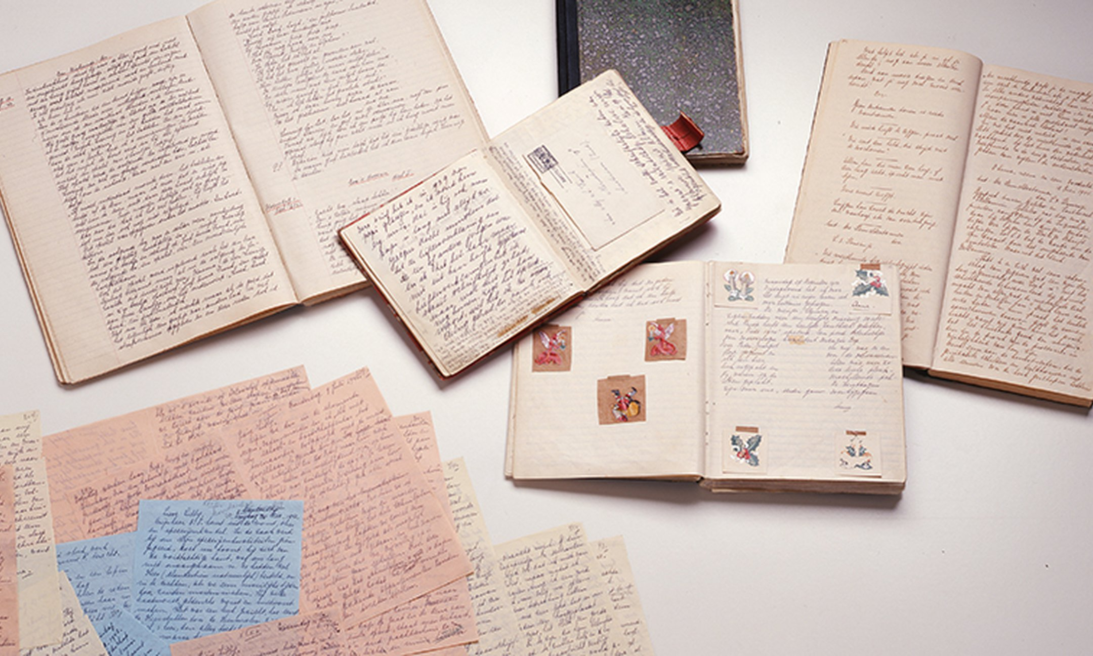 image of anne frank's diaries, open pages, loose letters, all laid out on display