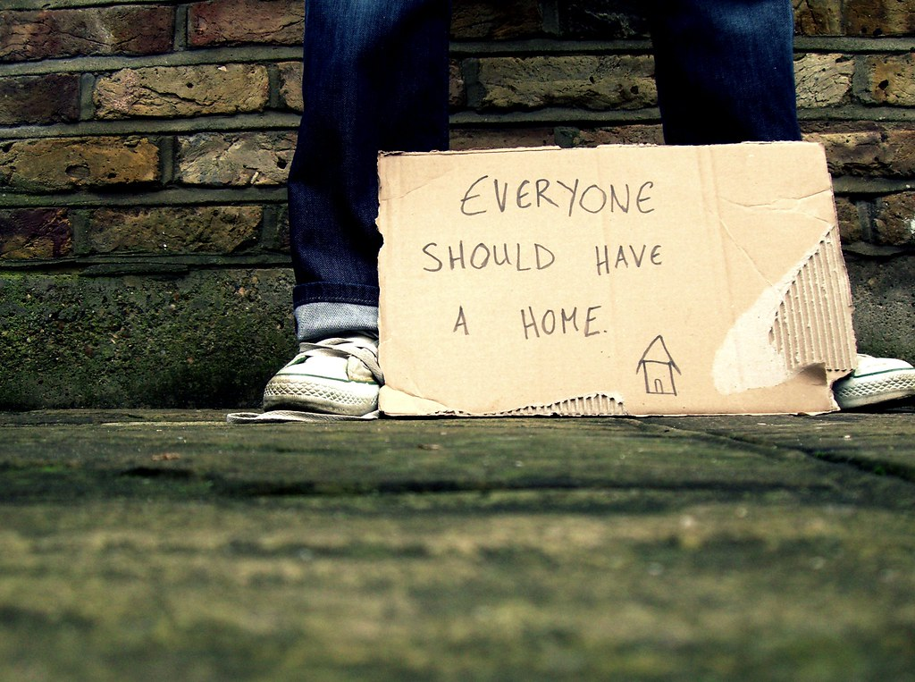 Image of a homeless person and a paper sign