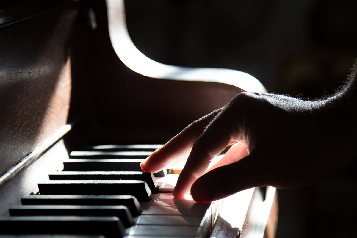 A hand on a piano keyboard.