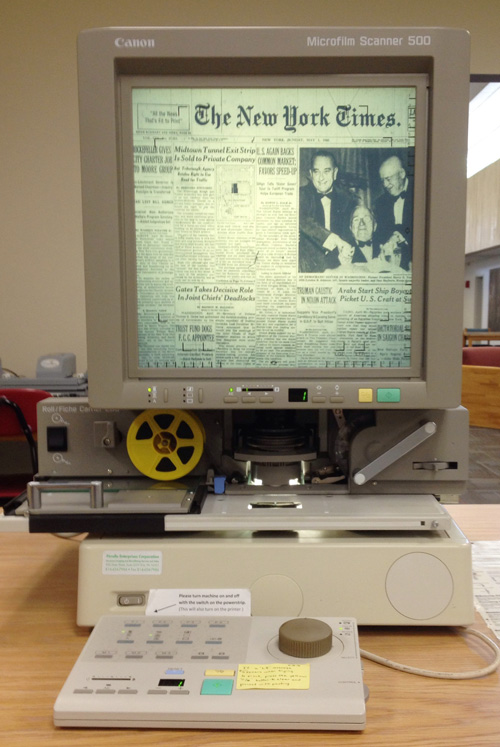 A photograph of a microfilm machine showing a page from The New York Times