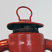 Close up of the top of a red kerosene lamp