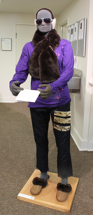 a mannequin wearing clothing made by the artist including fur earmuffs, a fur scarf, jeans with fur applique and fur slippers
