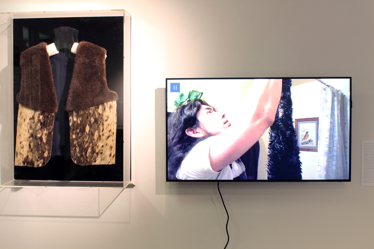 A vest made from seal and sea otter fur and a monitor playing a documentary film about the artists' process