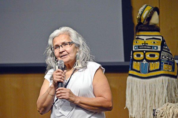 Lianna speaks into a microphone. A Chilkat robe is displayed in the background. (3-b Lianna Wallace)