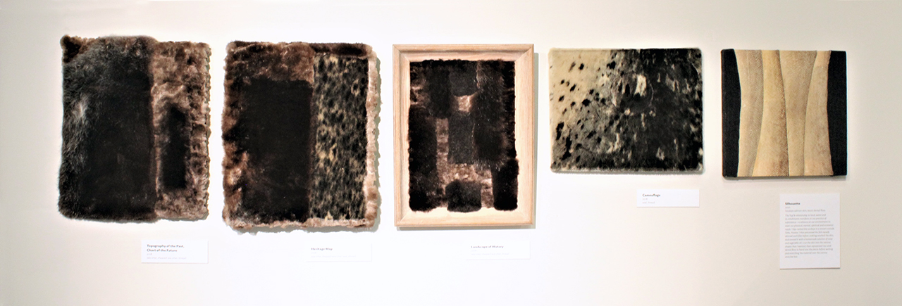 Five artworks shown: four paintings/sculptures made from sea otter and seal fur and one painting made from salmon skin