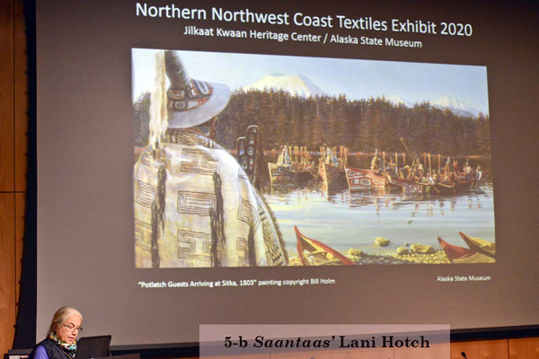 Lani Hotch at a podium giving a talk with slides about Northern Northwest Coast Textiles Exhibit 2020. (5-b Saantass' Lani Hotch)