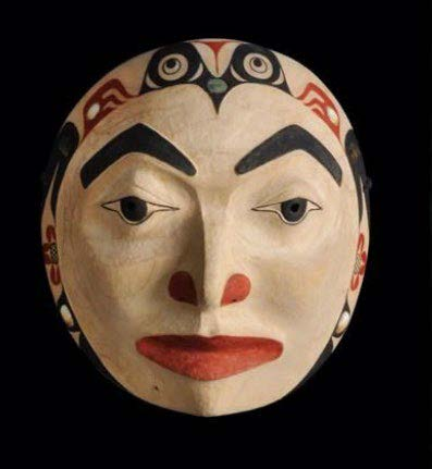 Mask carved to resemble a face with pronounced eyebrows, lips & nostrils Native formline decorates the edges.
