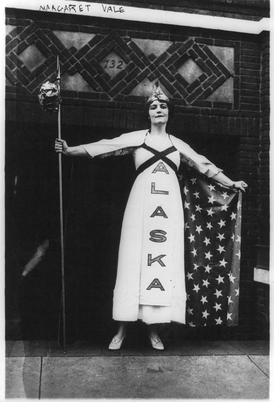 A young white woman wears a white dress that reads Alaska down the front. She wears a cape emblazoned with white stars. She wears a hat with a star pinned to the front. In her hand is a staff.