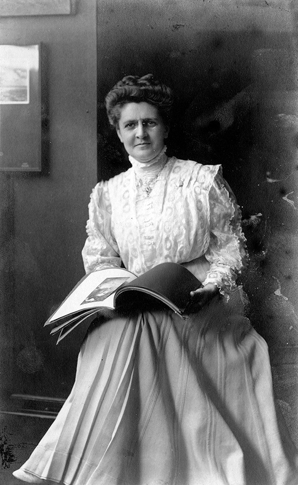 A middle age white women looks straight at the camera holding a book and wearing a long-sleeved lace dress.