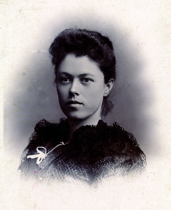 A young white woman with brown hair poses for a portrait.