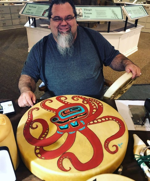 Abel Ryan shows of a drum he painted that depicts an octopus.