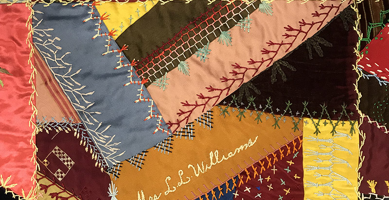 Quilt with warm collage of patchwork and fancy stitching.