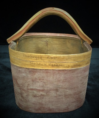 Squared-shaped bentwood bucket with bentwood handle.