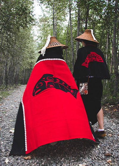 2 people pose with backs to camera to show off design on each robe.