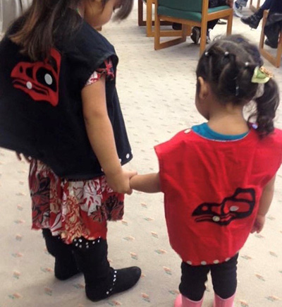 2 children showing off the back of their vests.