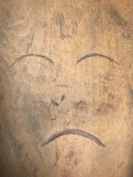 Carving of face with closed eyes and mouth turned down.