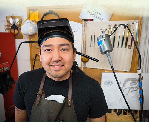 """Rico Worl in studio with brushes and sketches behind him. """"This is Tlingit Land"""" sign in background."""